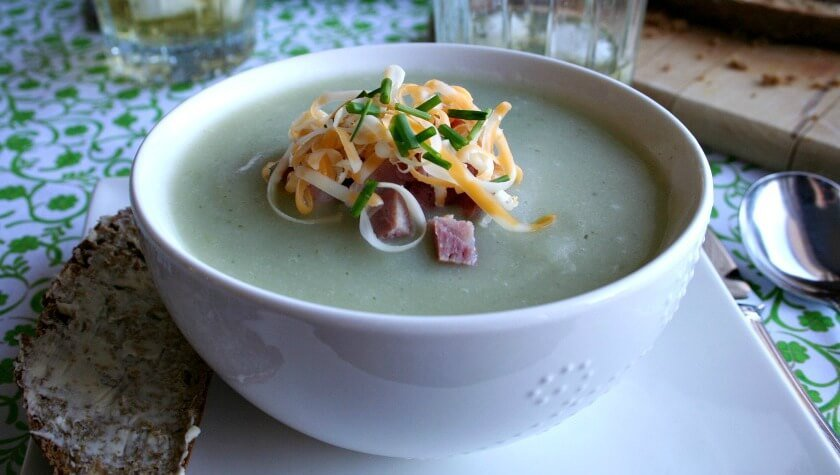 Bowl of potato soup garnished with chopped ham grated cheese and chives feature image